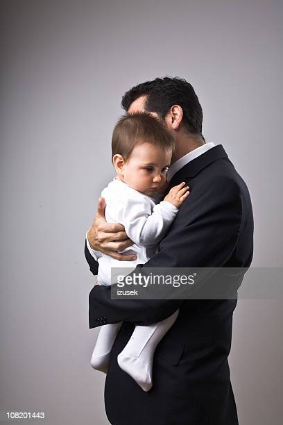 Man wearing suit holding a baby