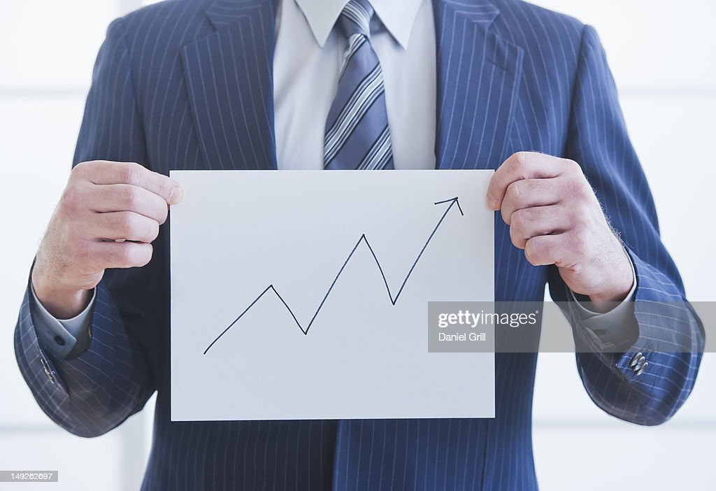 Man wearing suit holding chart : Stock Photo