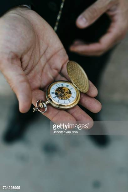 Man wearing suit, holding pocket watch in hand, elevated view, close-up