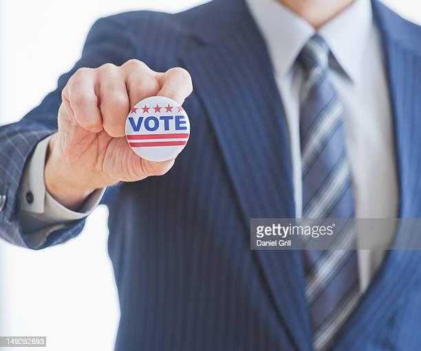 Man wearing suit holding vote pin