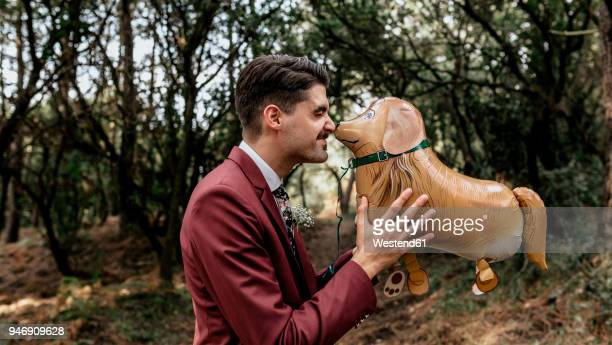 Man wearing suit in forest playing with funny dog-shaped balloon
