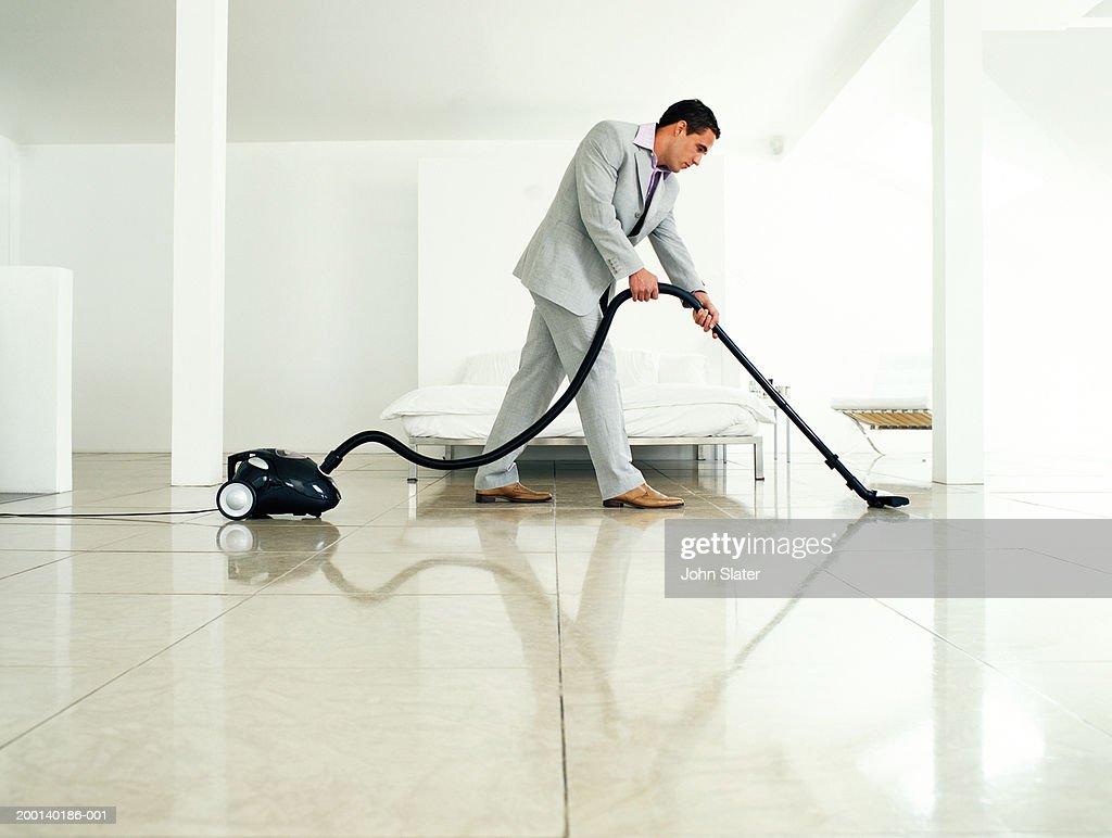 Man wearing suit vacuuming floor, side view : Foto de stock