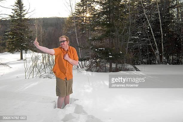 man wearing summer clothes, standing in snow, making obscene gesture - shorts stock-fotos und bilder