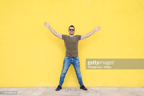 man wearing sunglasses and posing against a yellow wall - legs apart stock pictures, royalty-free photos & images