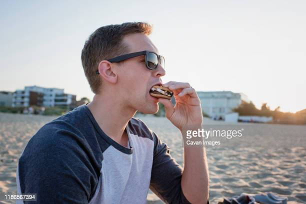 man wearing sunglasses eating smore at beach during sunset - chocolate stock pictures, royalty-free photos & images