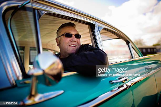 Man wearing sunglasses in vintage car