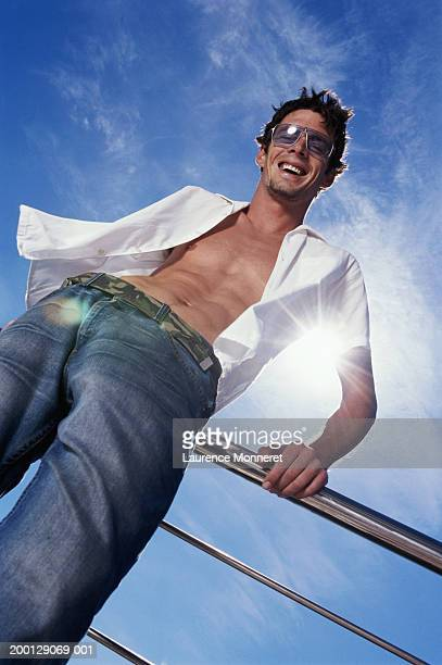 man wearing sunglasses leaning against railing, low angle view - fully unbuttoned stock pictures, royalty-free photos & images