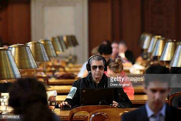 A man wearing sunglasses looks at his laptop inside the Rose Main Reading Room at the New York Public Library October 5 2016 in New York City The...