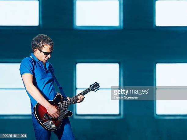 man wearing sunglasses playing guitar - モダンロック ストックフォトと画像