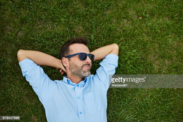 man wearing sunglasses relaxing on a meadow, top view - gente serena foto e immagini stock