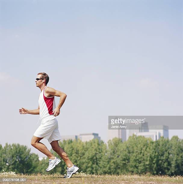 Man wearing sunglasses running in field, side view