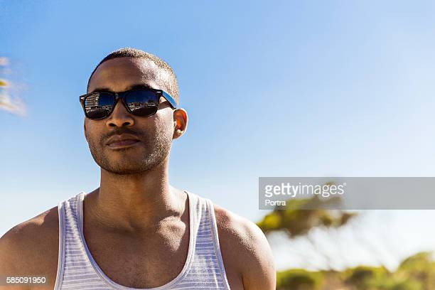 man wearing sunglasses standing against clear sky - sleeveless stock pictures, royalty-free photos & images