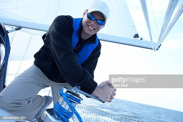 Man wearing sunglasses turning winch handle on yacht, smiling