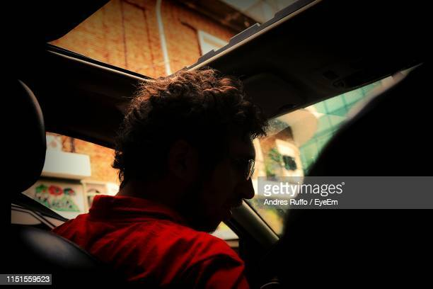 man wearing sunglasses while sitting in car - andres ruffo stock pictures, royalty-free photos & images
