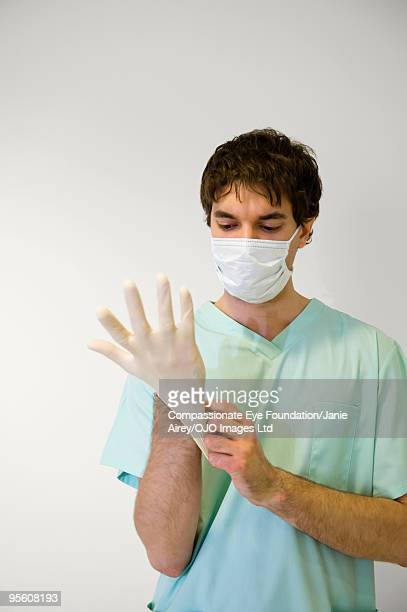 man wearing surgical mask putting on rubber glove
