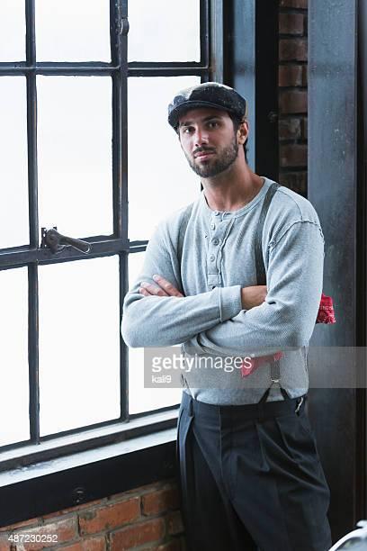 HOMME DEBOUT près de la fenêtre avec bretelles