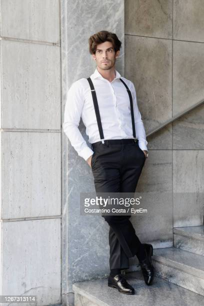 man wearing suspenders while standing by wall - サスペンダー ストックフォトと画像