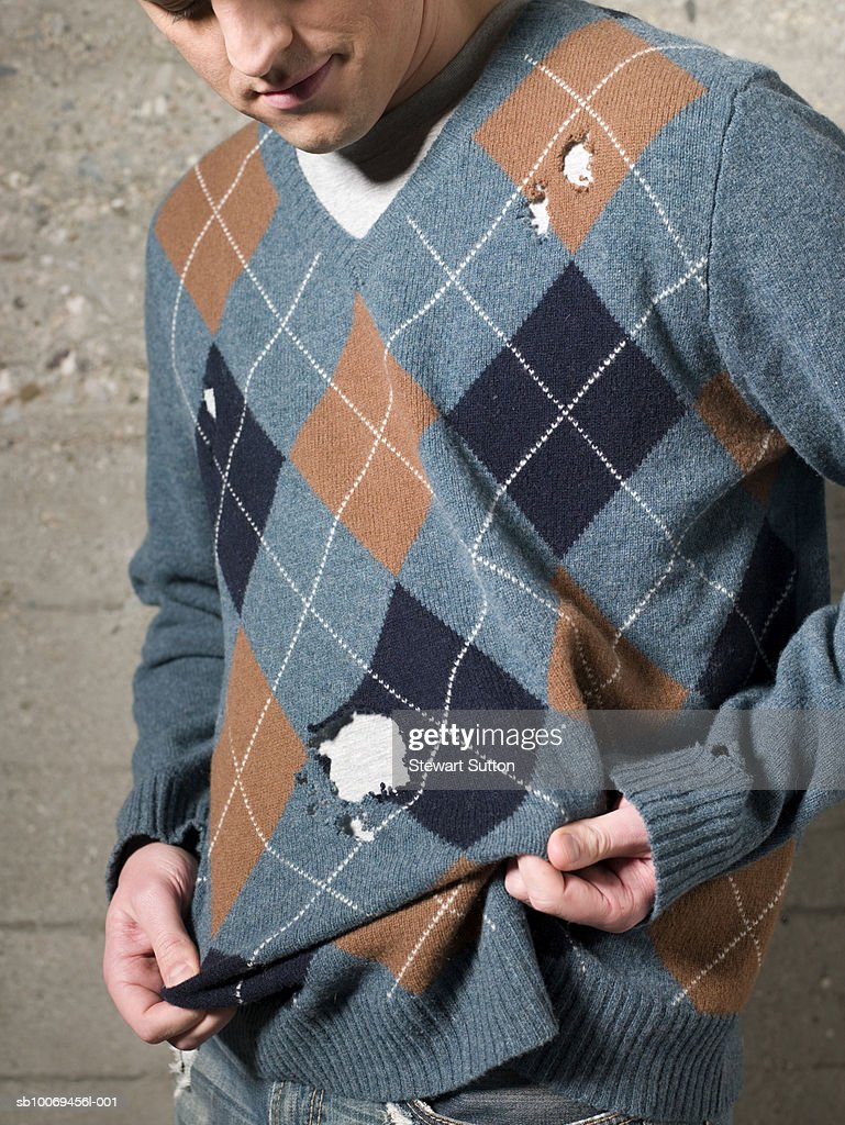 Man wearing sweater with holes, outdoors : Stock Photo