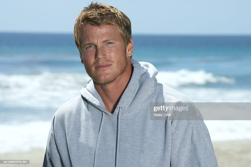 Man wearing sweatshirt on beach, smiling, portrait : Foto stock