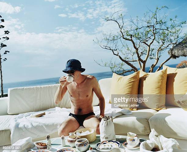 man wearing swimsuit sitting on outdoor couch, drinking coffee - young men in speedos stock pictures, royalty-free photos & images