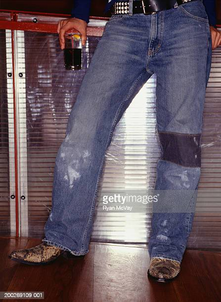 Man wearing tattered jeans and snakeskin boots, Close-up of legs