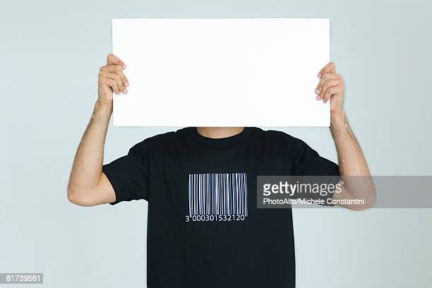man wearing tee-shirt with bar code, holding blank sign in front of face - blank sign stock photos and pictures