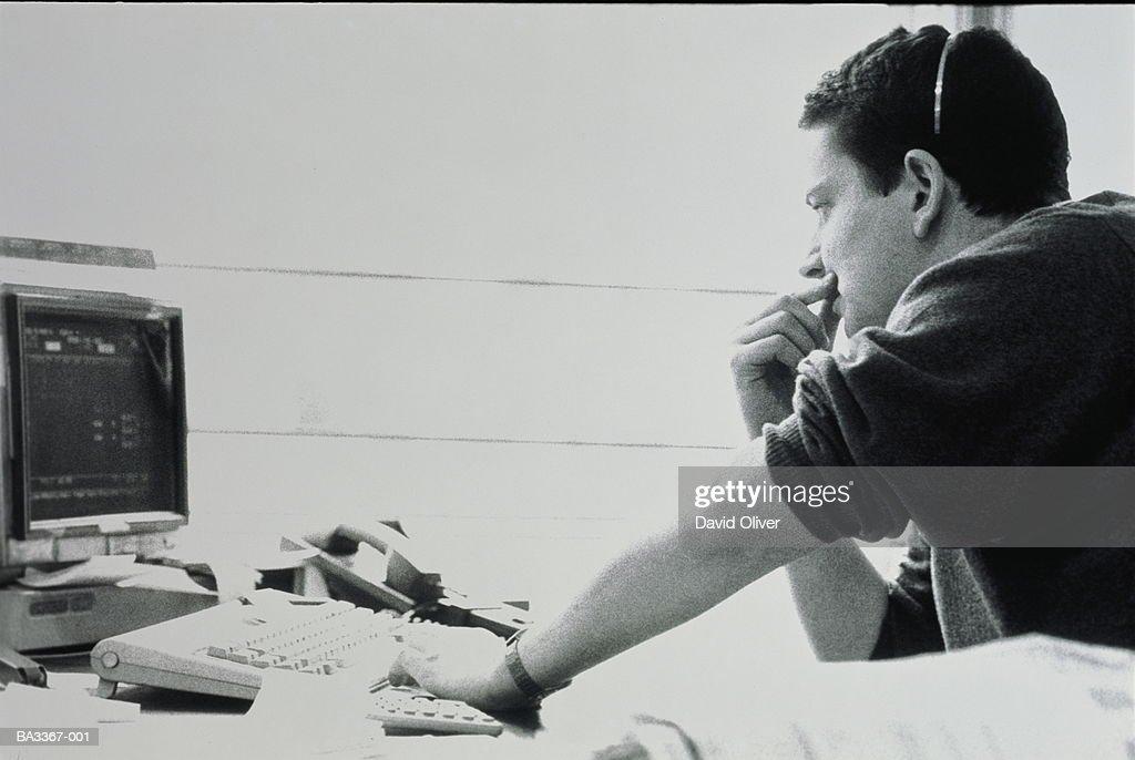 Man wearing telephone headset, sitting at computer terminal (b&w) : ストックフォト