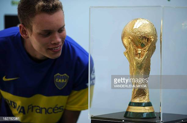 A man wearing the Argentine Boca Juniors football club jersey watches the FIFA World Cup 2014 trophy brought to Brazil by former Brazilian crack Cafu...