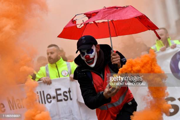 TOPSHOT A man wearing the DC comic Joker character's mask and waving a smoke bomb takes part in a demonstration to protest against the pension...