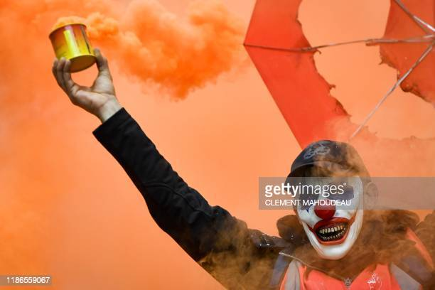 A man wearing the DC comic Joker character's mask and waving a smoke bomb takes part in a demonstration to protest against the pension overhauls in...