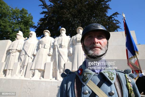 A man wearing the uniform of a French WWI soldier or Poilu stands by the World War I memorial They Shall Not Pass during a ceremony with the French...