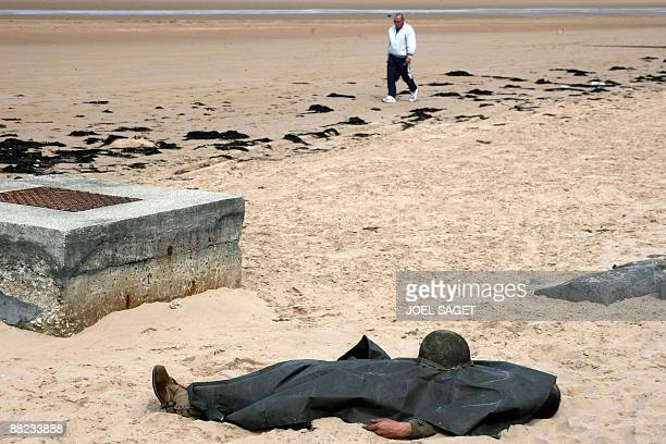 A man wearing the uniform of a World War II US soldier pretends to be dead during a reconstruction of June 1944 events at Omaha Beach in...