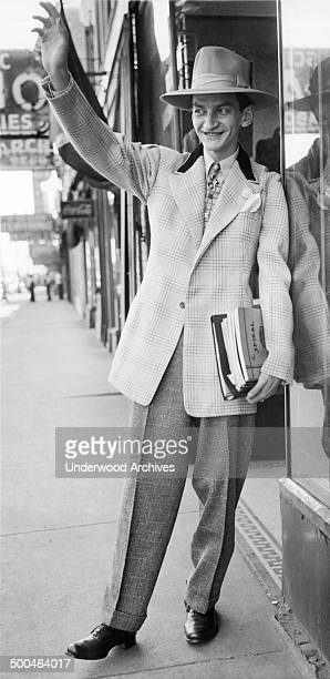 A man wearing the very latest in zootsuit styles and a hat to match Chicago Illinois September 24 1943 The new style reflects War Production Board...
