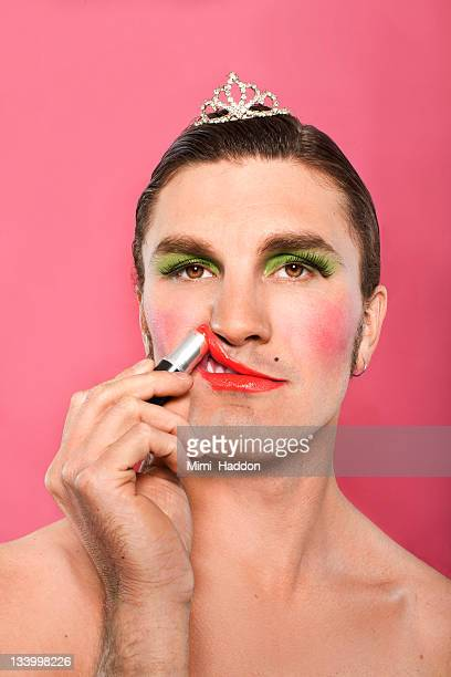 man wearing tiara and make up putting on lipstick - cross dressing stock photos and pictures