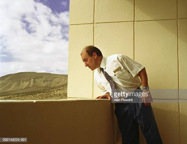 Man wearing tie looking over side of balcony