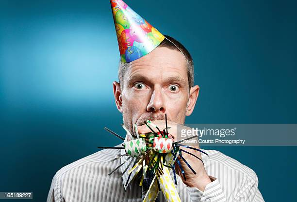 man wearing tie with party hat and horn blowers - party blower stock pictures, royalty-free photos & images