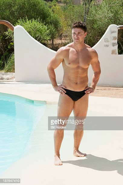 Man wearing tight swimsuit by pool