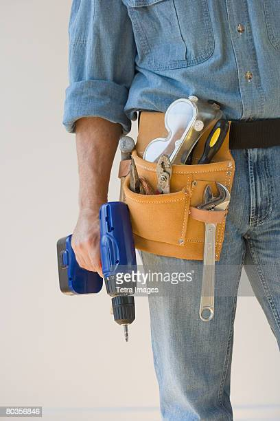 Man wearing tool belt and holding drill