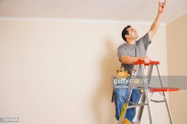 man wearing tool belt on ladder changing light bulb - mid adult men fotografías e imágenes de stock