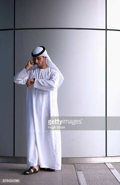 man wearing traditional clothing checking time and using mobile phone - hugh sitton stock pictures, royalty-free photos & images