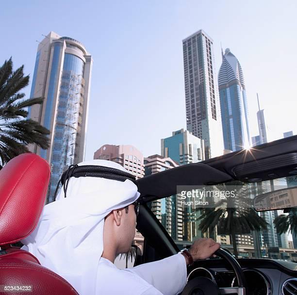 man wearing traditional clothing driving sports car on sheikh zayed road, dubai, u.a.e - hugh sitton stock-fotos und bilder