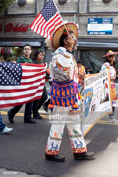 CONTENT] A man wearing traditional clothing is seen holding a US flag while marching down Olympic Blvd in Los Angeles California Hundreds march in...