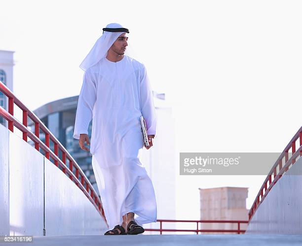 man wearing traditional clothing walking on walkway - hugh sitton stockfoto's en -beelden