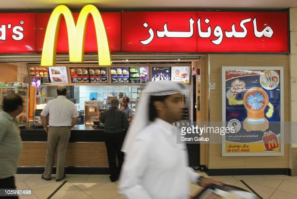 A man wearing traditional local clothes carries a tray of food from a McDonald's fast food restaurant in the City Center shopping mall in West Bay...