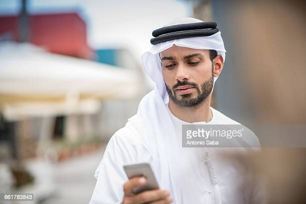man wearing traditional middle eastern clothing reading smartphone text, dubai, united arab emirates - united arab emirates stock pictures, royalty-free photos & images