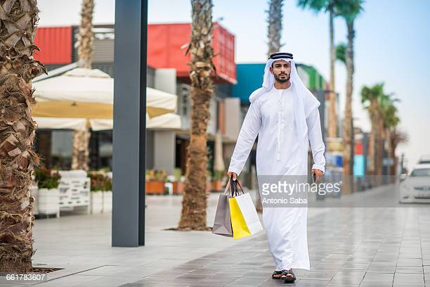 man wearing traditional middle eastern clothing walking along street carrying shopping bags, dubai, united arab emirates - gulf countries stock pictures, royalty-free photos & images