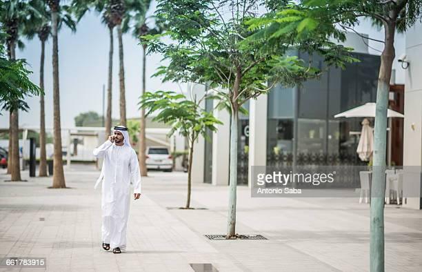 Man wearing traditional middle eastern clothing walking along street talking on smartphone, Dubai, United Arab Emirates