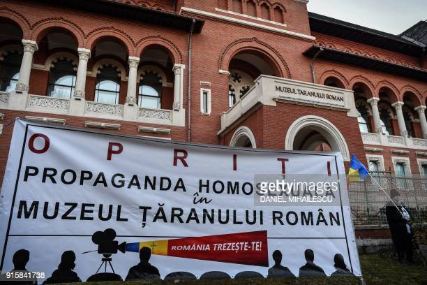 A man wearing traditional Romanian outfits holds a flag next to a banner reading 'STOP homosexual propaganda at The Romanian Peasant's Museum' during...