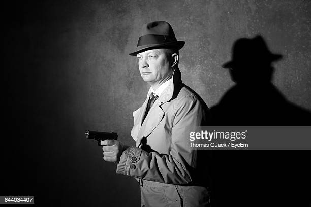man wearing trench coat and hat pointing gun at night - film noir style stock pictures, royalty-free photos & images