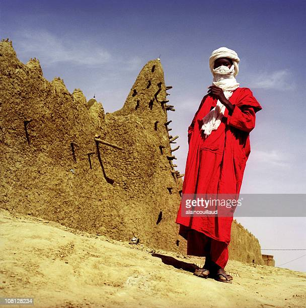 man wearing tuareg and red tunic in desert village - tuareg tribe stock pictures, royalty-free photos & images